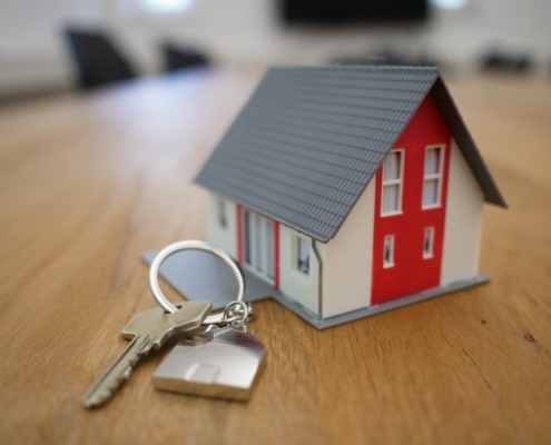 A small model house with a set of keys, indicating a new house move.